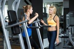 Deux femmes blondes sportives parlant dans le gymnase La fille communique avec l'entraîneur Photographie stock