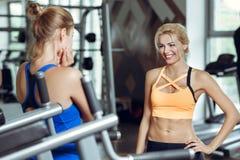 Deux femmes blondes sportives parlant dans le gymnase La fille communique avec l'entraîneur Photos libres de droits