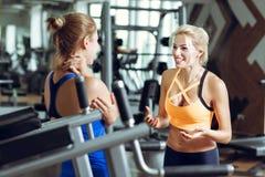 Deux femmes blondes sportives parlant dans le gymnase La fille communique avec l'entraîneur Photos stock