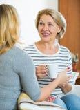 Deux femmes buvant du thé et parlant à l'intérieur domestique Images libres de droits