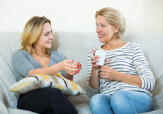 Deux femmes buvant du thé et parlant à l'intérieur domestique Image libre de droits