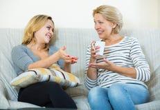 Deux femmes buvant du thé et parlant à l'intérieur domestique Photo stock