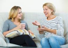 Deux femmes buvant du thé et parlant à l'intérieur domestique Image stock