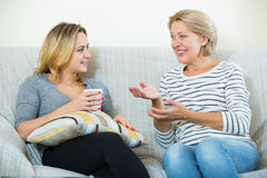 Deux femmes buvant du thé et parlant à l'intérieur domestique Images stock