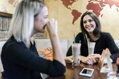 Deux femmes buvant et parlant en café Photo stock