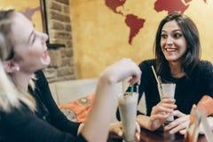 Deux femmes buvant et parlant en café Photographie stock