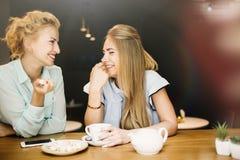 Deux femmes buvant et parlant en café tout en profitant d'un agréable moment Images stock