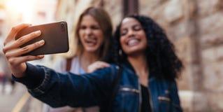 Deux femmes cliquant sur un selfie dehors Image stock