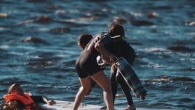 Deux femmes combattant avec les tapis roulés se tenant sur le conseil surfant dans l'eau onduleuse banque de vidéos