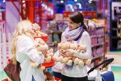 Deux femmes comme les ajouter ou les amis gais à la voiture d'enfant blanche est jouante et obtenante l'amusement par l'ours de j Image stock