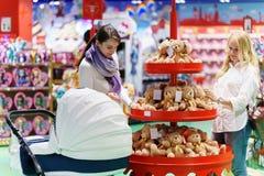 Deux femmes comme les ajouter ou les amis gais à la voiture d'enfant blanche recherche un certain ours de jouet dans le grand sup Photos stock