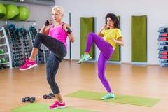 Deux femmes convenables faisant l'exercice de coup de pied de jambe droite tout en établissant dans le gymnase Images libres de droits