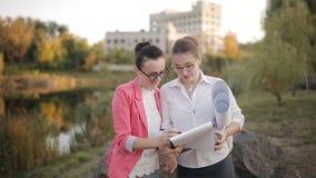 Deux femmes conviennent sur la documentation pour la fourniture des matériaux de construction pour l'achèvement de la constructio banque de vidéos