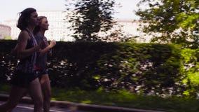 Deux femmes courant dans la ville près de la rivière banque de vidéos