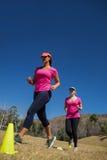 Deux femmes courant par des cônes dans le camp de botte photographie stock