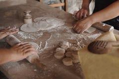 Deux femmes déroulent la pâte sur une table en bois Le cadre est seulement des mains du ` s de femmes photo stock
