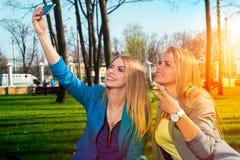 Deux femmes détendant en parc Photographie stock