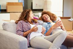 Deux femmes détendant sur la nouvelle maison de Sofa With Hot Drink In Photographie stock libre de droits