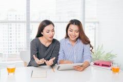 Deux femmes d'affaires asiatiques de sourire travaillant avec l'ordinateur portable dans le bureau Image stock