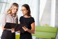 Deux femmes d'affaires ayant le contact informel dans le bureau moderne Images libres de droits