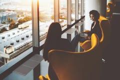 Deux femmes d'affaires ayant le travail se réunissant près des fenêtres de bureau photographie stock libre de droits