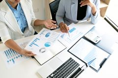 Deux femmes d'affaires de chef discutant les diagrammes et les graphiques donnant les résultats photographie stock