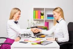 Deux femmes d'affaires fermant l'affaire avec la poignée de main Photos stock
