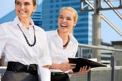 Deux femmes d'affaires heureuses avec des dépliants photographie stock libre de droits