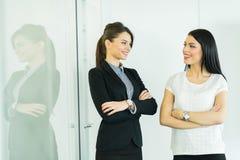 Deux femmes d'affaires parlant dans un bureau avec la réflexion image libre de droits