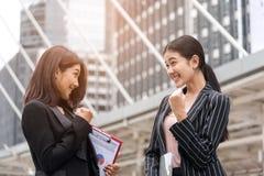 Deux femmes d'affaires remettent l'augmenter heureux à extérieur, aux affaires pour réaliser et au concept réussi image libre de droits