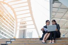 Deux femmes d'affaires s'asseyent sur l'escalier et parlent des affaires avec l'ordinateur portable Photos libres de droits