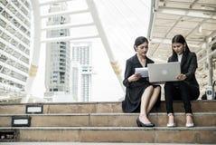 Deux femmes d'affaires s'asseyent sur l'escalier et parlent des affaires avec l'ordinateur portable et copient l'espace pour le t Photo stock