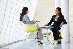Deux femmes d'affaires se réunissant autour du Tableau dans le bureau moderne photographie stock libre de droits