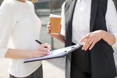 Deux femmes d'affaires sur se réunir dehors près de l'immeuble de bureaux Image libre de droits