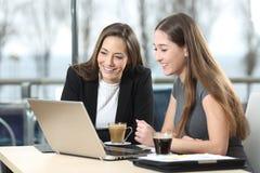 Deux femmes d'affaires travaillant sur la ligne dans une barre photographie stock