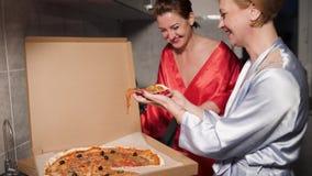 Deux femmes d'amies mangeant de la pizza et appr?ciant une causerie de soir?e avant l'extinction - une robe bleue de port de mati banque de vidéos