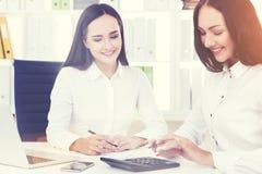 Deux femmes dans des chemises blanches fonctionnant dans le bureau Photographie stock libre de droits