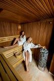 Deux femmes dans la détente centrale de bien-être dans le sauna en bois Photos libres de droits