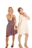 Deux femmes dans la main de prise de sourire de robes photographie stock libre de droits