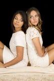 Deux femmes dans la robe blanche sur le noir de nouveau au regard arrière de retour Photo libre de droits