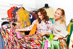 Deux femmes dans la salle d'exposition choisissant des vêtements Photo stock