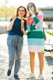 Deux femmes dans la ville marchant ensemble - se dirigeant photographie stock