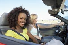 Deux femmes dans le convertible sur la route de désert Image libre de droits