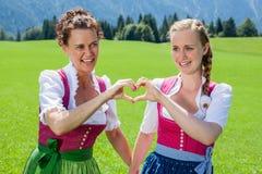 Deux femmes dans le dirndl formant un coeur avec ses mains Image libre de droits