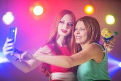 Deux femmes dans une boîte de nuit sous le projecteur avec un cocktail dedans Images stock