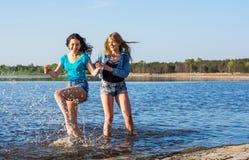 Deux femmes dansent et éclaboussent l'eau sur un bord de la mer, riant Photographie stock