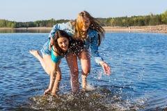 Deux femmes dansent et éclaboussent l'eau sur un bord de la mer, riant Photo stock