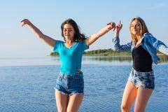 Deux femmes dansent sur le bord de la mer, tenant les mains et le laughin Photos stock