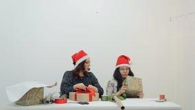 Deux femmes décorent des cadeaux avec des rubans pour Noël, nouvelle année banque de vidéos