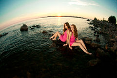 Deux femmes de beauté sur la plage au coucher du soleil. Appréciez la nature. Gi de luxe Photo stock